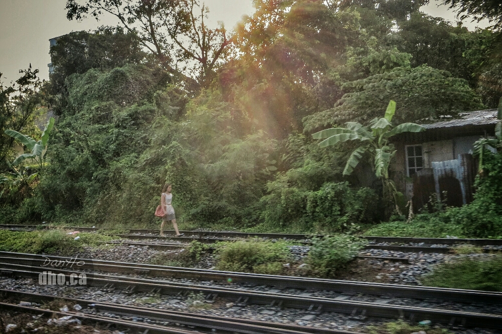 A lady walks on the tracks, presumably on her way home, in Bangkok, Thailand.